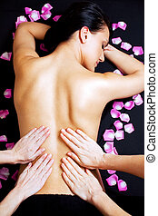Lower back massage - Four female hands giving a lower back...