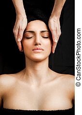Femal facial massage - beautiful young female receiving...