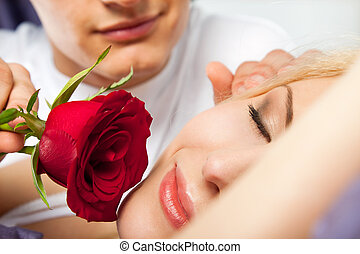 Morning couple rose - young male romantically waking up a...