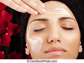 Applying face cream - female hand applying moisturizing...