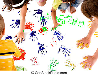 Kids hand prints - kids making colourful hand prints on...