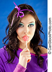 Woman licking lollipop - Young beautiful woman licking...