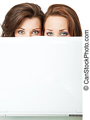 girls peeking behind laptop - Two beautiful young females...