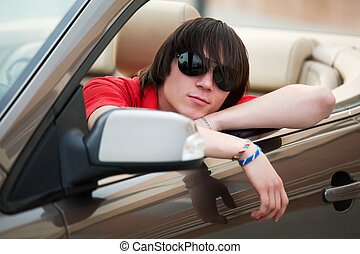 Young man in a convertible - Young man sitting in a...