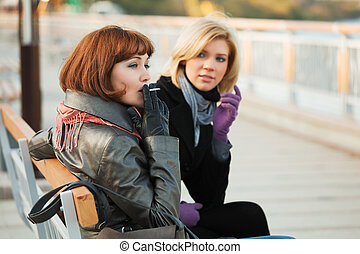 Two young women sitting on a bench.