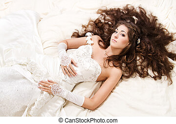 Bride with curly long hair lying over white. High angle...