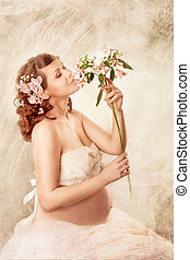 Pregnant woman sniffing flowers and dreaming Sitting with...