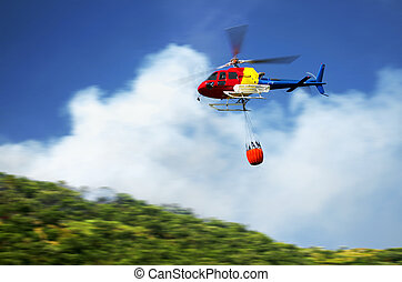 Firefighter helicopter in action flying over a fire in the...