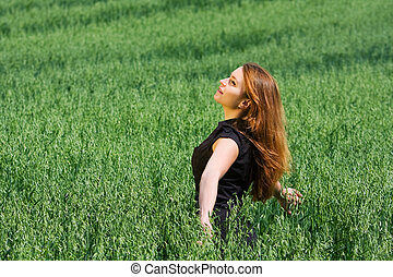 Happy young woman in a field - Happy young woman relaxing in...