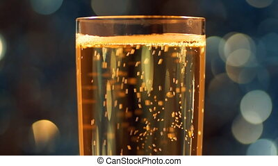 Glass of sparkling wine with lights in bokeh