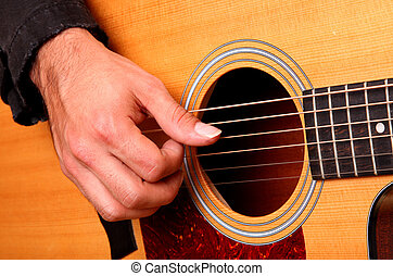 playing guitar - Hands of man playing an acoustic guitar...