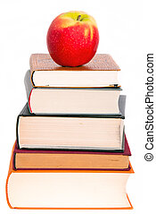 an apple on a book pile - a juicy apple lies on a book pile