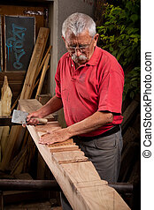 woodcarver working with mallet and chisel - Old woodcarver...