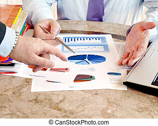 Business meeting - Closeup of hands with financial charts at...