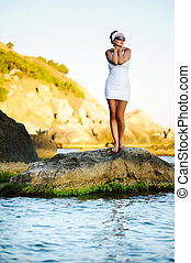 woman standing on a stone in the sea