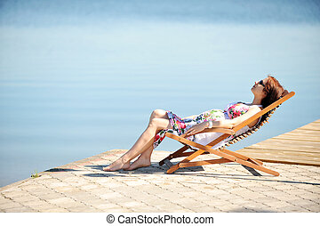 woman on lakeside - woman sitting in lounge chair summers...