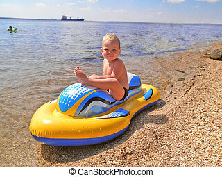 The kid at sea on an inflatable boa