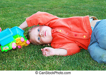 Baby lying on the grass with a toy