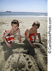 building a sandcastle - two cute boys building a sandcastle
