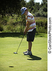 boy playing golf - cute young boy playing golf