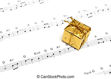 Music - A small golden present on top of some sheetmusic