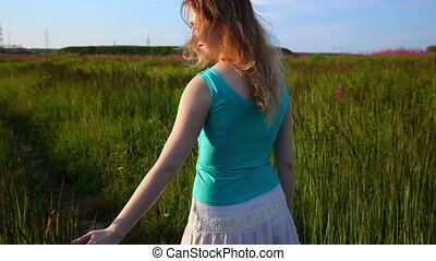 Young woman walking on summer field.