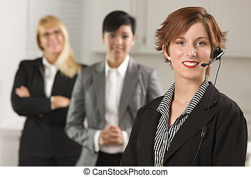 Pretty Red Haired Businesswoman with Headset and Colleagues