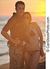 surf couple posing at beach on sunset - romantic couple in...