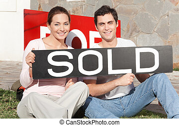 Couple Purchase New Home - Happy couple sitting against...