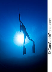 A girl spearfishing infront of the sun - A young girl...