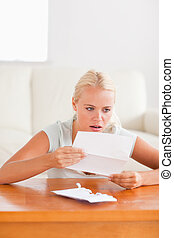 Woman looking at a letter in shock in her living room
