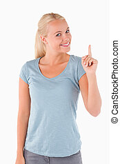 Smiling gorgeous woman pointing at copyspace in a studio