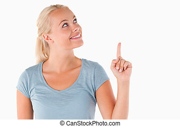 Smiling blond woman pointing at copyspace