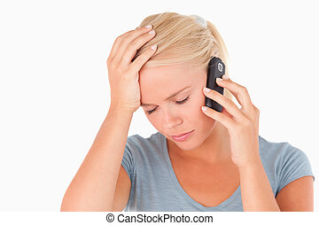 Sad blond woman on a phone in a studio