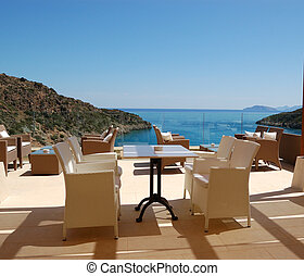Chairs at sea view relaxation area of luxury hotel, Crete, Greece