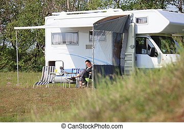 Mobile Home - Woman sitting outside a campervan reading