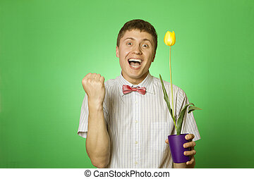 Man holding a tulip grown in a pot
