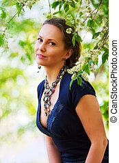 Beautiful woman among blossoming trees. - Portrait of young...