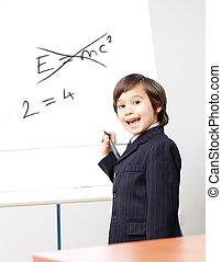 Genius little boy writting E=mc2 on the board, new formula...