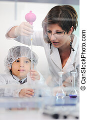 Smart cute little male child  experimenting in lab with his mother doctor scientist
