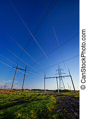 Crossing wires - Electric power lines in a field over blue...