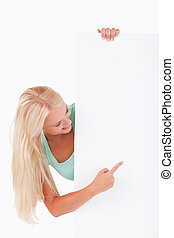 Blond-haired woman pointing at a whiteboard
