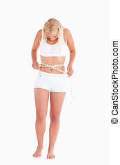 Young blond woman measuring her waist