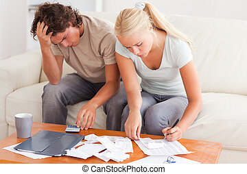 Worn out couple working together in the living room