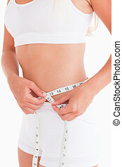 Fit woman measuring her waist