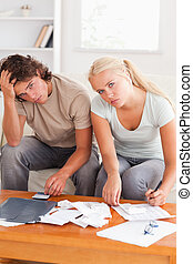 Despaired stressed couple calculating their expenses