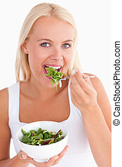 Gorgeous woman eating salad in a studio