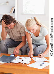 Despaired couple calculating their expenses