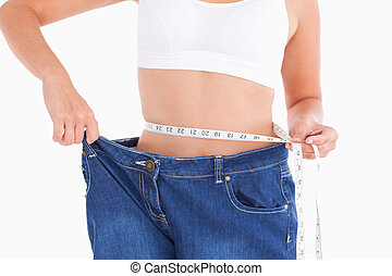 Woman measuring her waist while wearing too big jeans