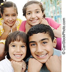 Vertical photo of children group, four friends smiling outdoor, boys and girls closeup